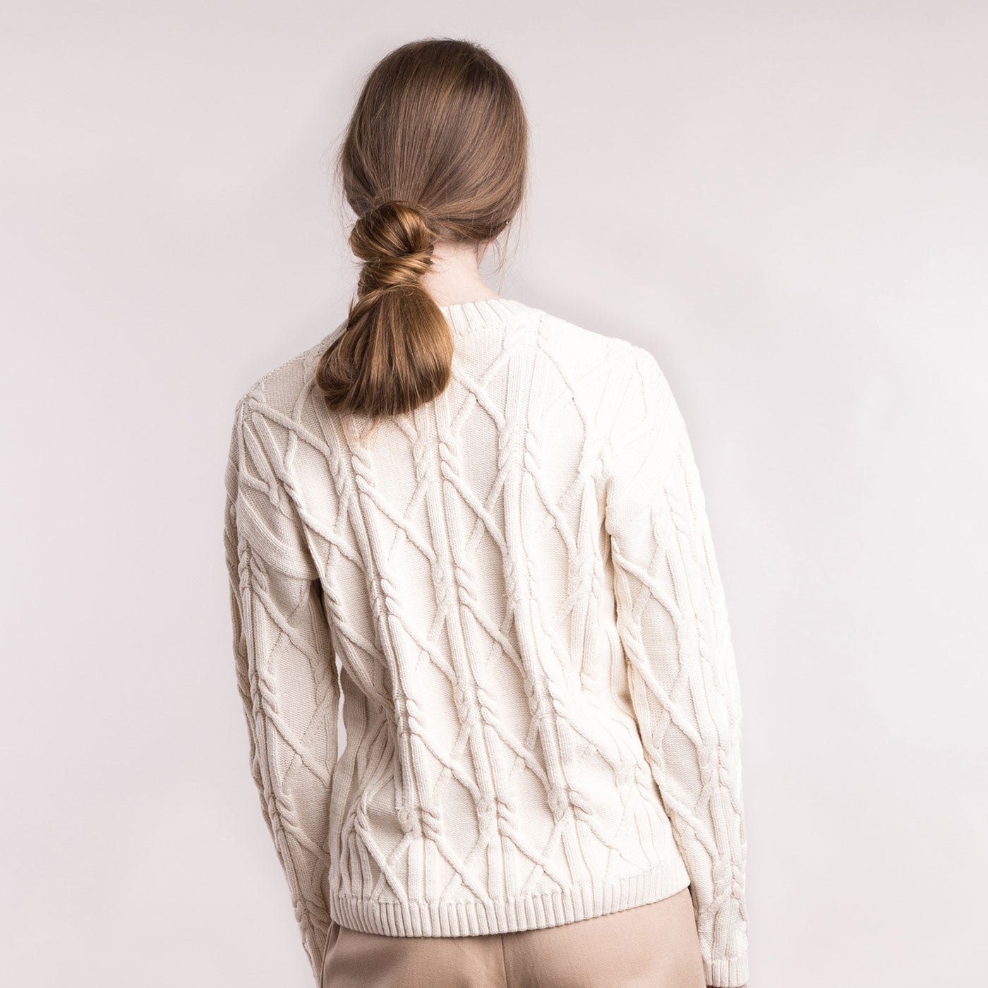 The model wears a cream sustainable organic cotton knitted aran pullover, back view.
