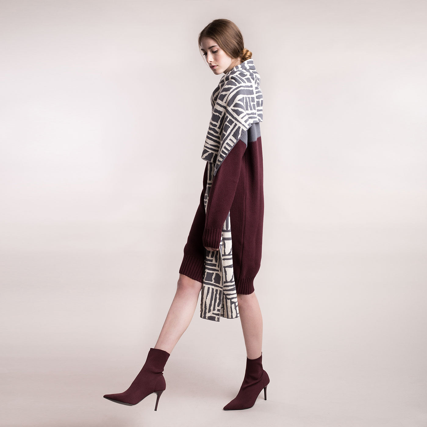The model wears a grey and cream, sustainable organic cotton, knitted arty bricks scarf, side view.