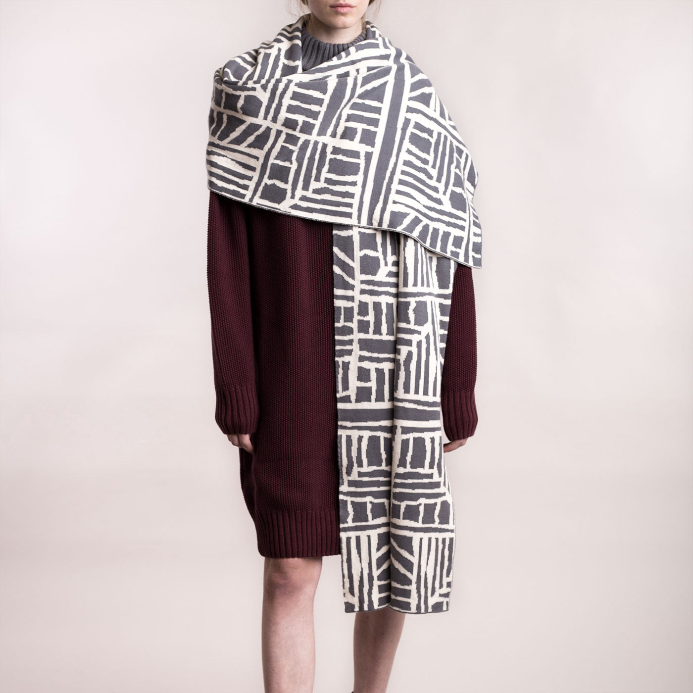 The model wears a grey and cream, sustainable organic cotton, knitted arty bricks scarf, close up front.