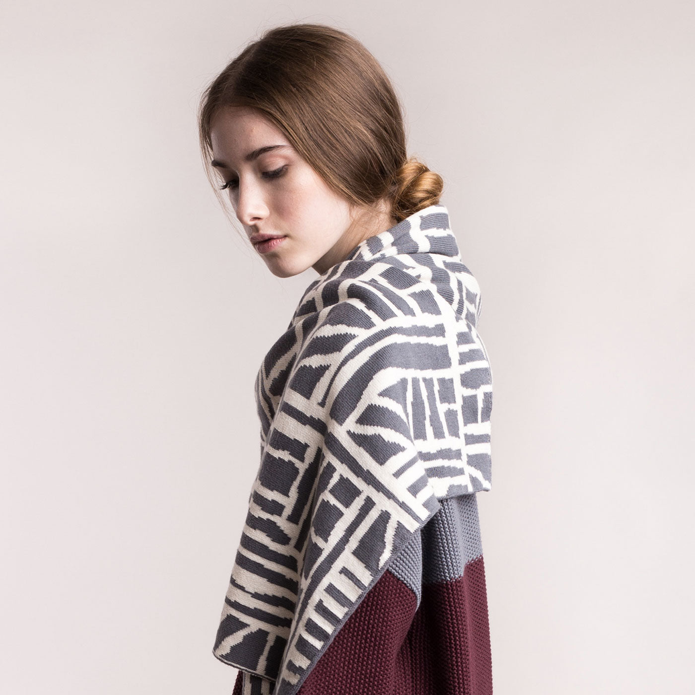 The model wears a grey and cream, sustainable organic cotton, knitted arty bricks scarf, looks to the side.