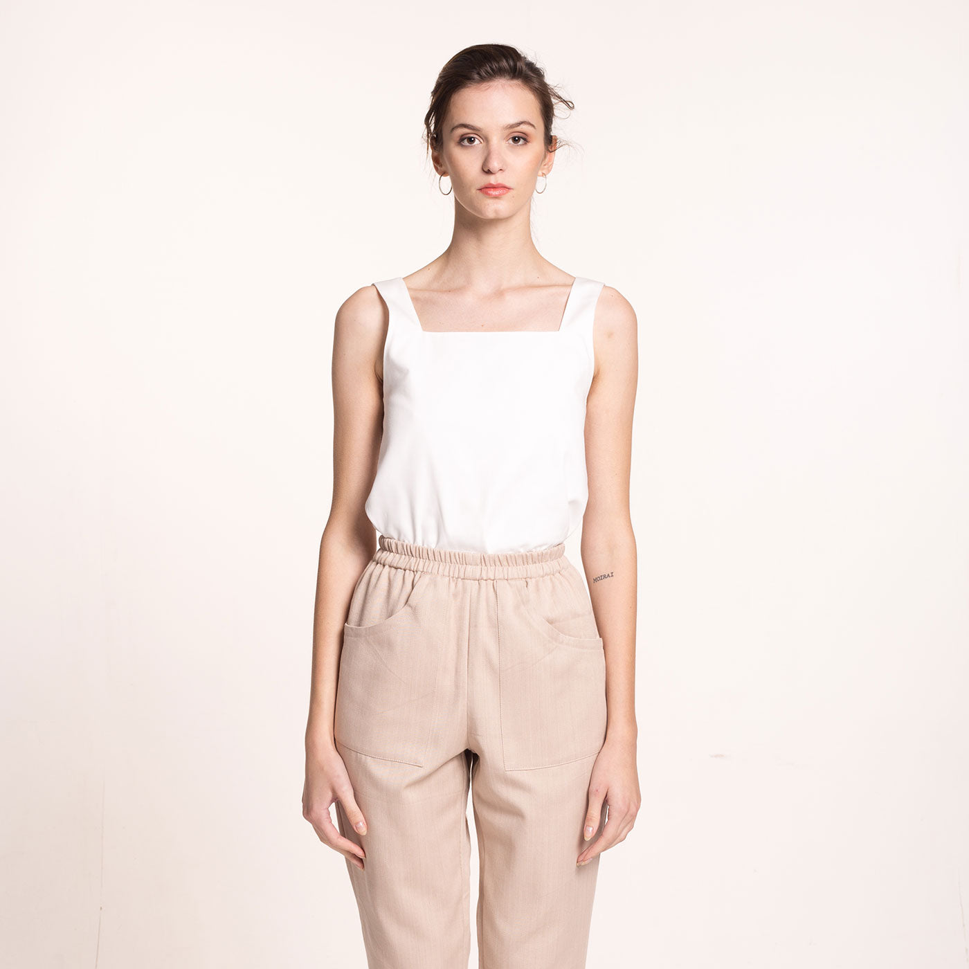 The model wears a white, sustainable, organic cotton, wide straps top, front view.