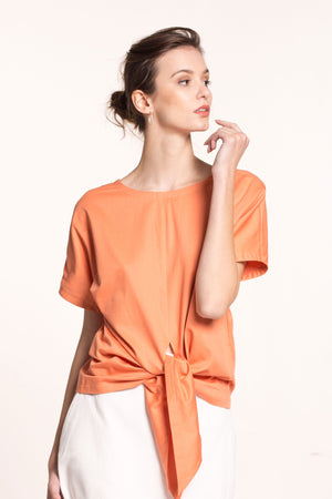 The model wears an orange, front tie, sustainable, organic cotton sateen top, with short sleeves and round neckline.