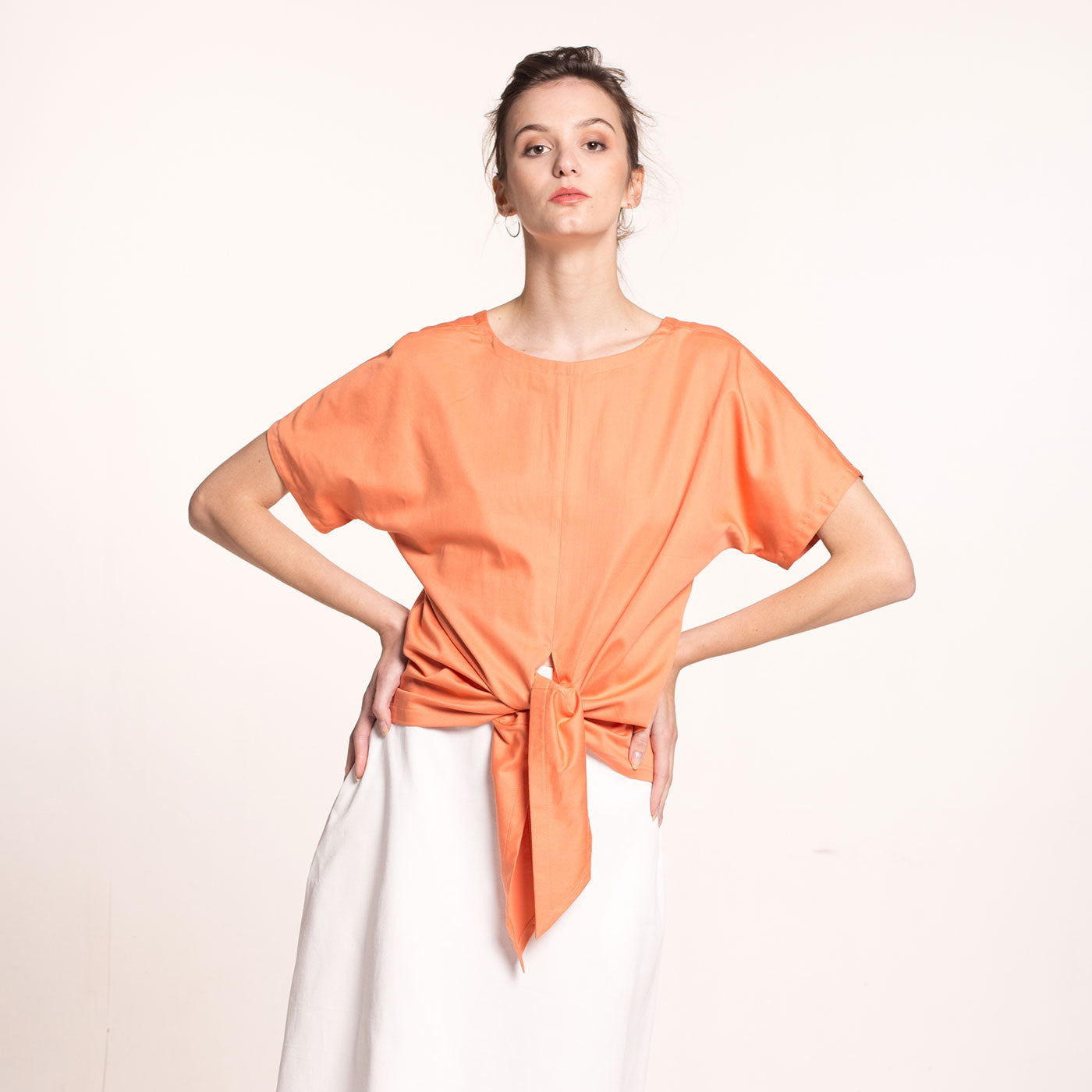 e model wears an orange, front tie, sustainable, organic cotton sateen top, with short sleeves and round neckline, front view.