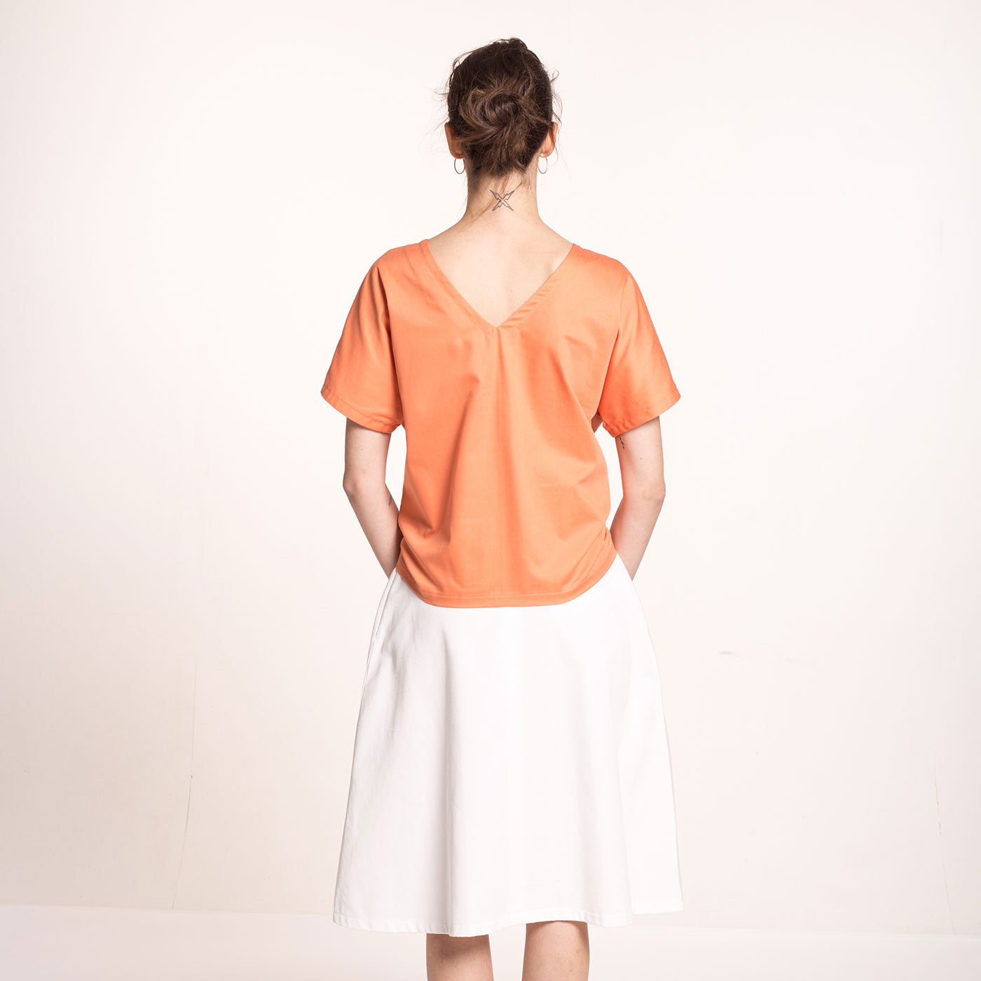 e model wears an orange, front tie, sustainable, organic cotton sateen top, with short sleeves V-neck at the back, back view.