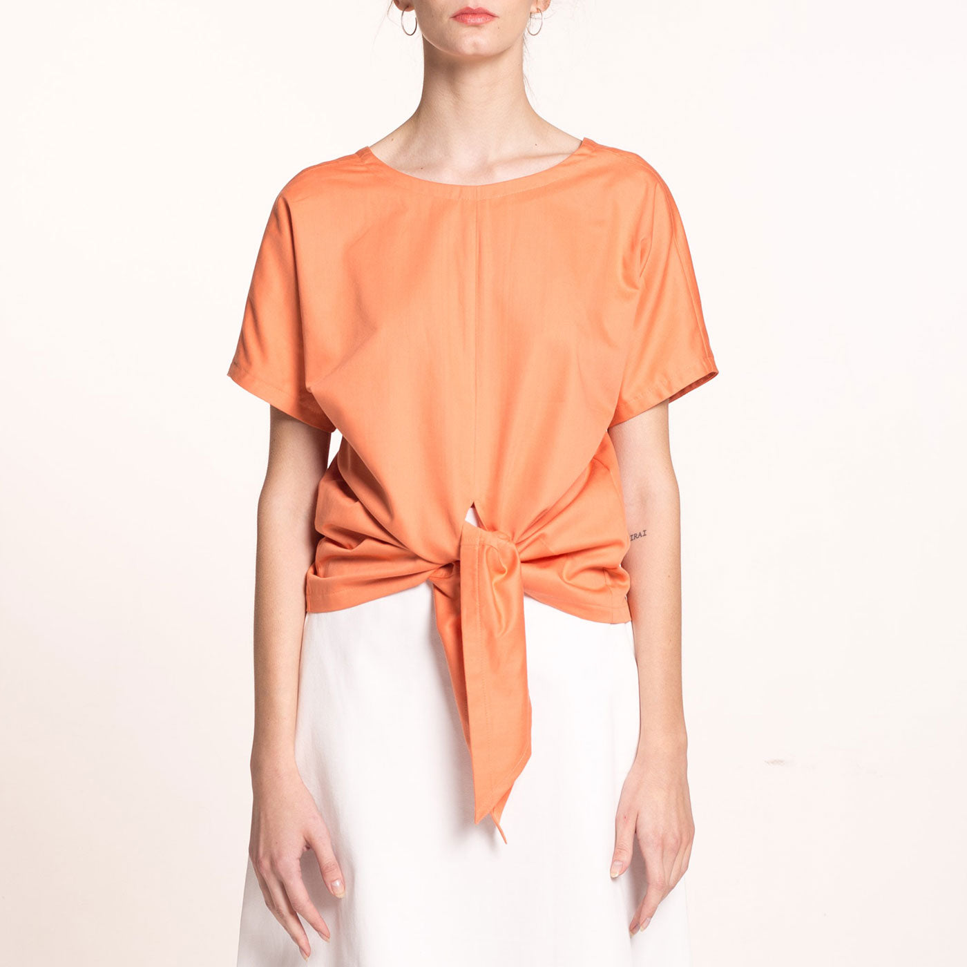 e model wears an orange, front tie, sustainable, organic cotton sateen top, with short sleeves and round neckline on the front.