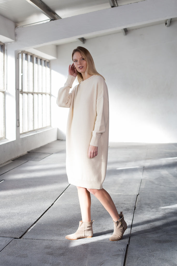 The model wears a natural, sustainable organic cotton knitted fine rice dress with low neck and knee lenght.
