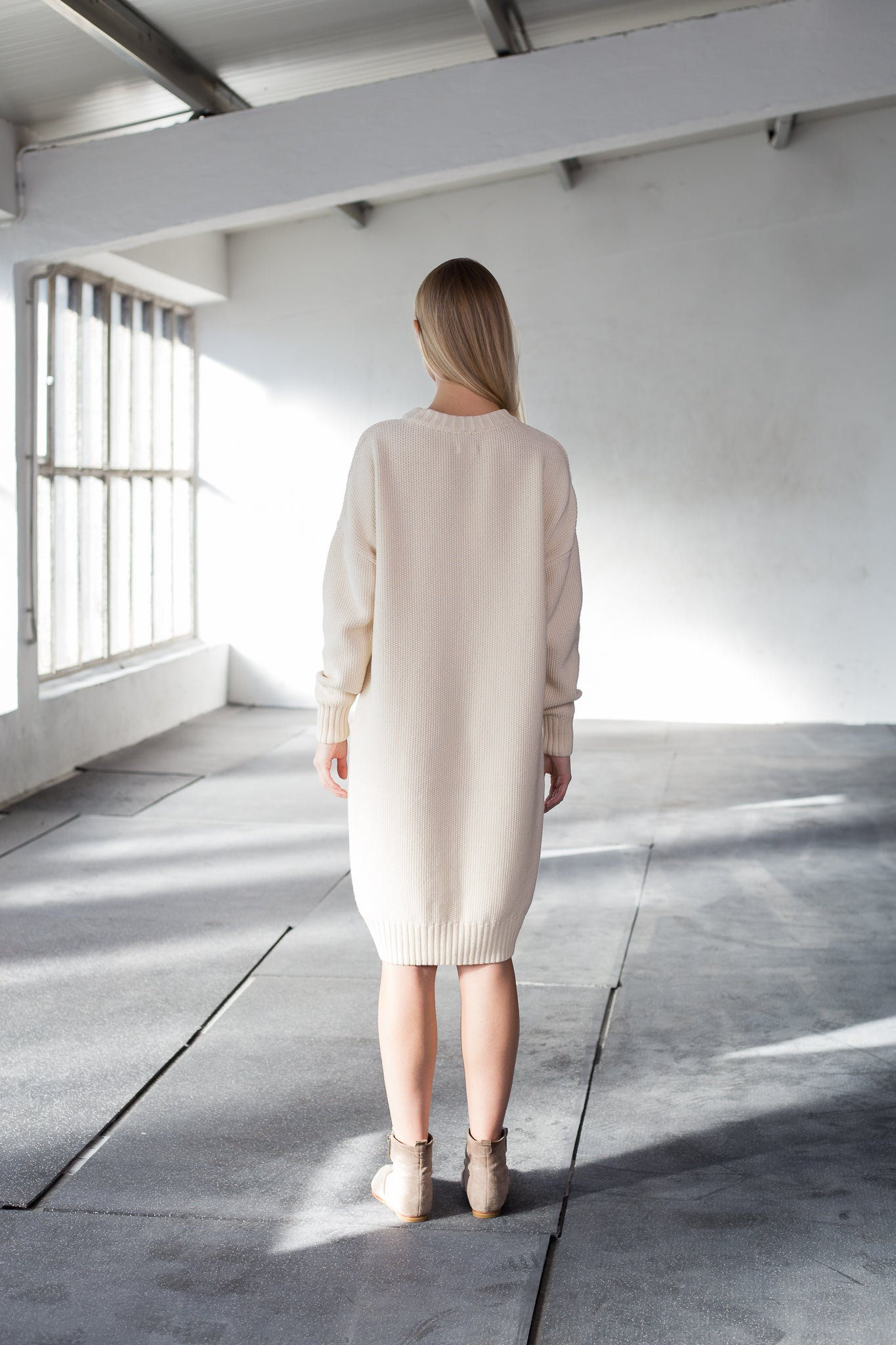 The model wears a natural, sustainable organic cotton knitted fine rice dress with low neck and knee lenght, back view.