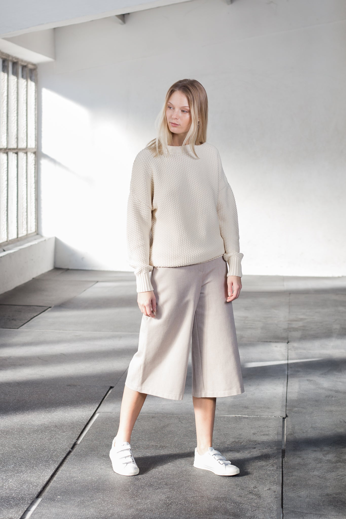 The model wears a natural sustainable organic cotton knitted rice cubes pullover and a skirt..