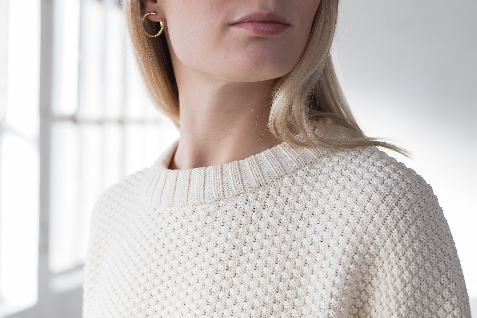 The model wears a natural sustainable organic cotton knitted rice cubes pullover with low neck.