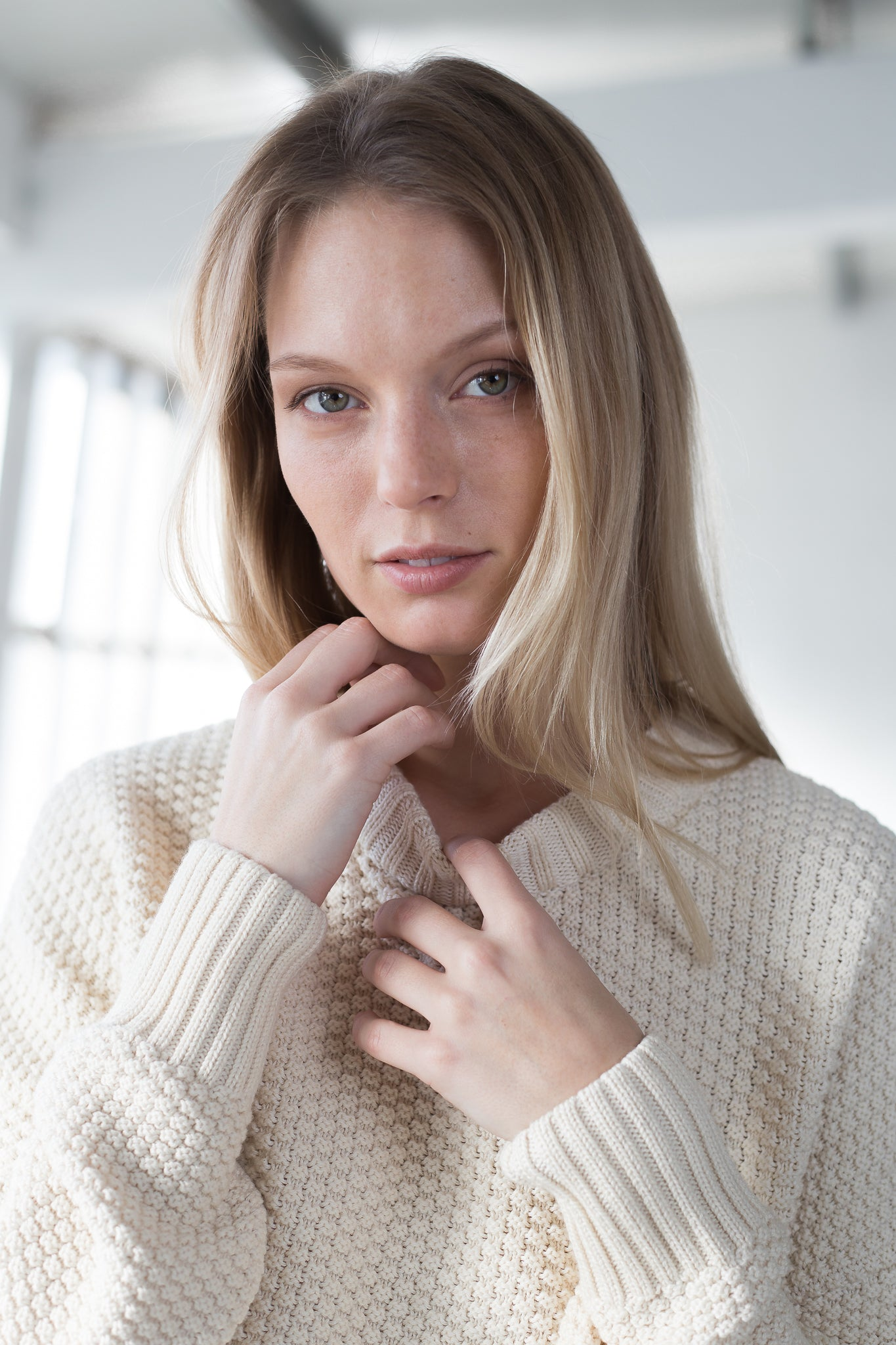 The model wears a natural sustainable organic cotton knitted rice cubes pullover with low neck, frontal view.