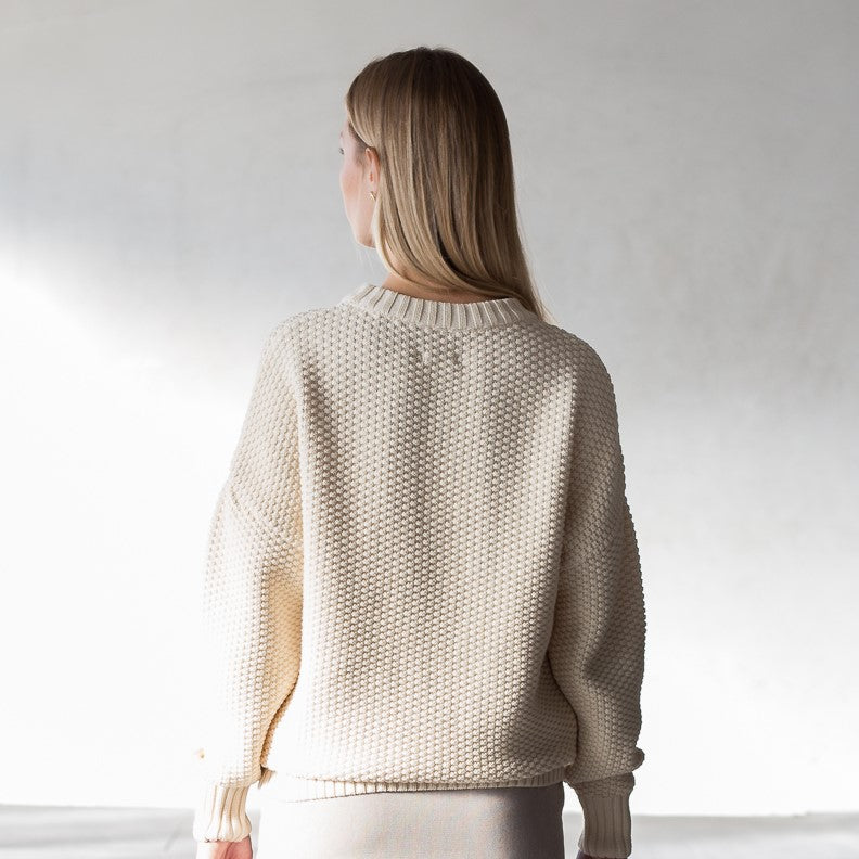 The model wears a natural sustainable organic cotton knitted rice cubes pullover, back view.