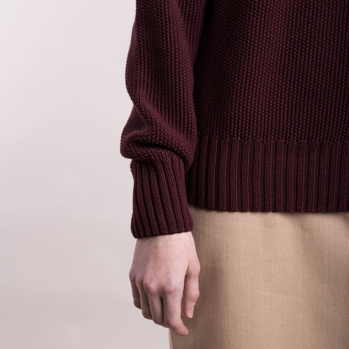 The model wears a burgundy sustainable organic cotton knitted fine rice pullover, detail of the sleeve..