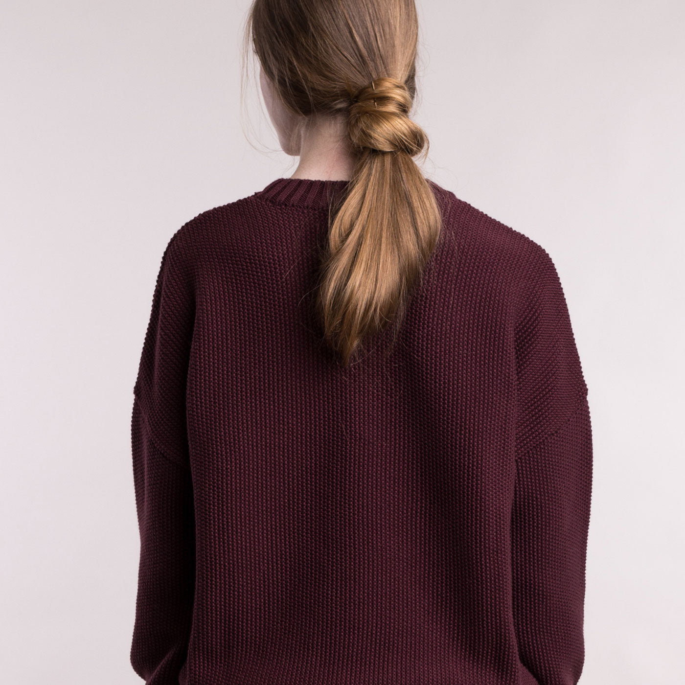 The model wears a burgundy sustainable organic cotton knitted fine rice pullover, back view.