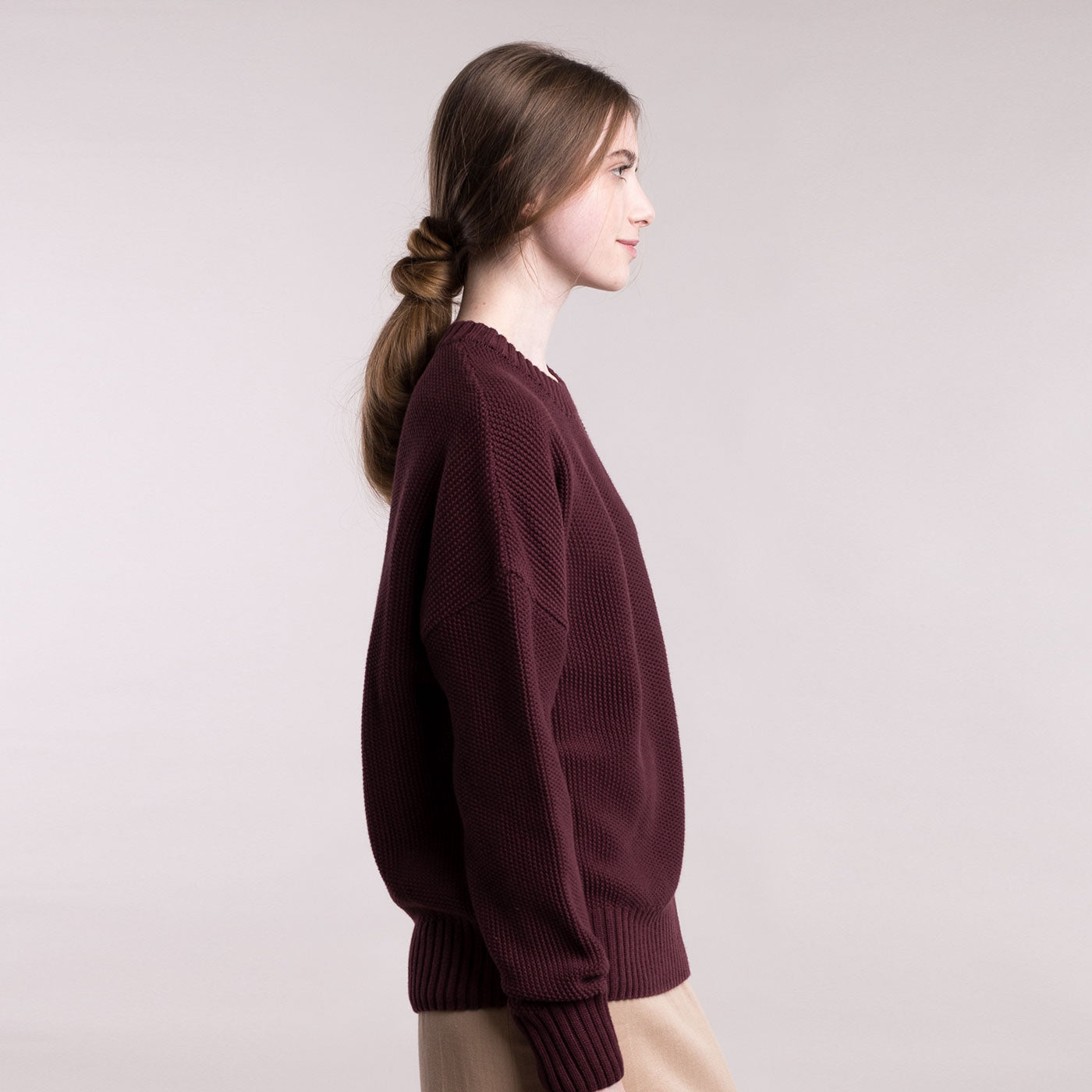 The model wears a burgundy sustainable organic cotton knitted fine rice pullover, side view.