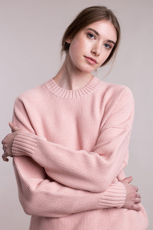 The model wears a dusty pink sustainable organic cotton knitted fine rice pullover, frontal view.