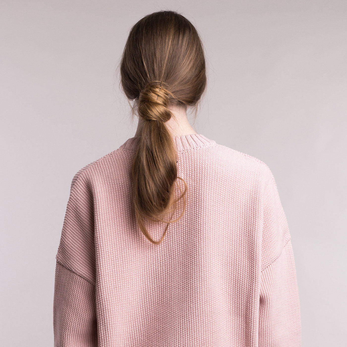 The model wears a dusty pink sustainable organic cotton knitted fine rice pullover, back view.