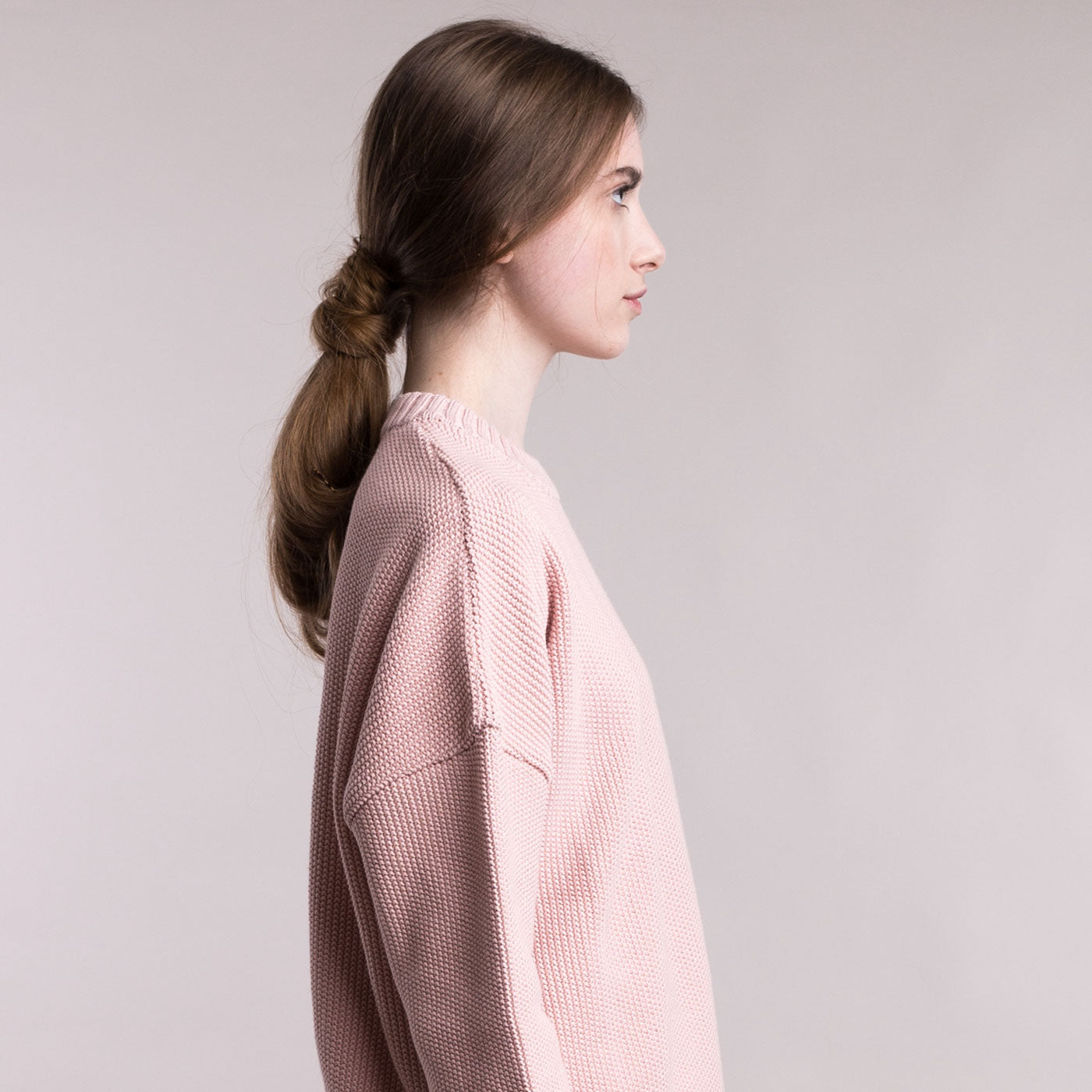 The model wears a dusty pink sustainable organic cotton knitted fine rice pullover, side view.