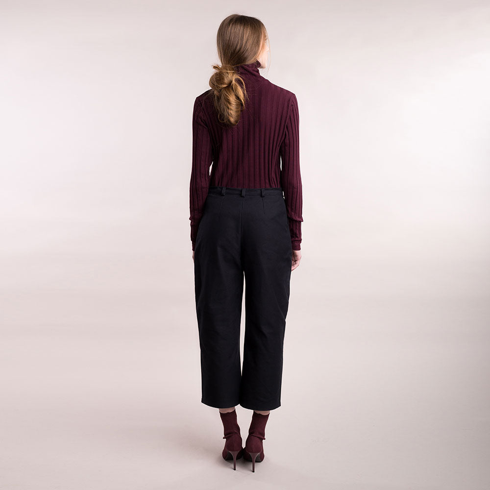 The model wears black, sustainable organic cotton, wide-leg trousers, back view.