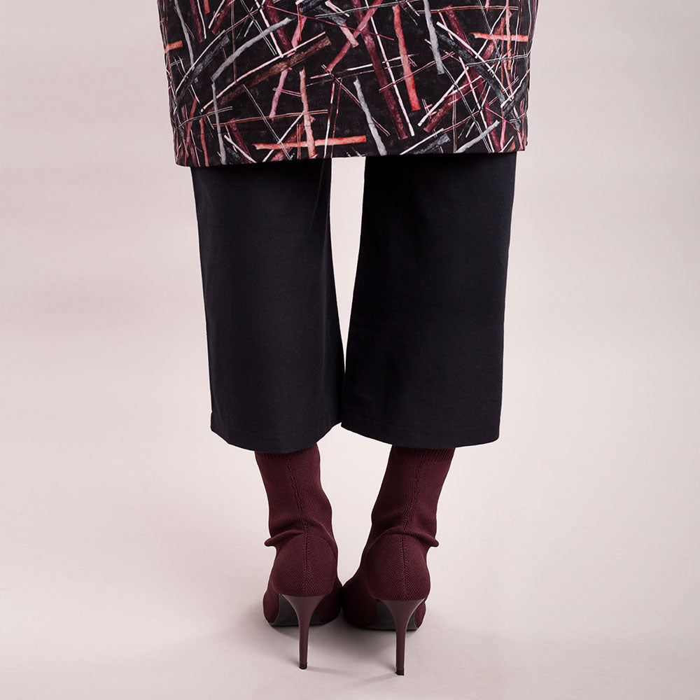 The model wears black, sustainable organic cotton, wide-leg trousers, back view, close up.
