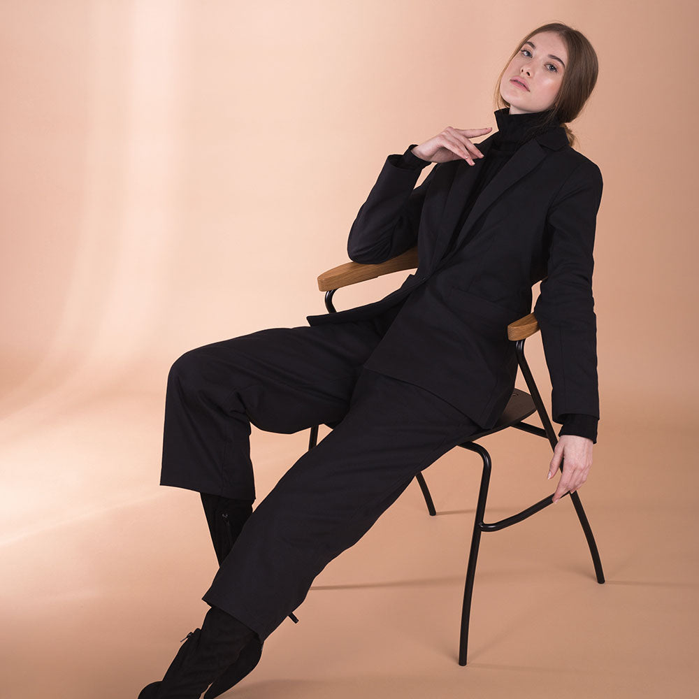 The model wears black, sustainable organic cotton, wide-leg trousers and sits on a chair.