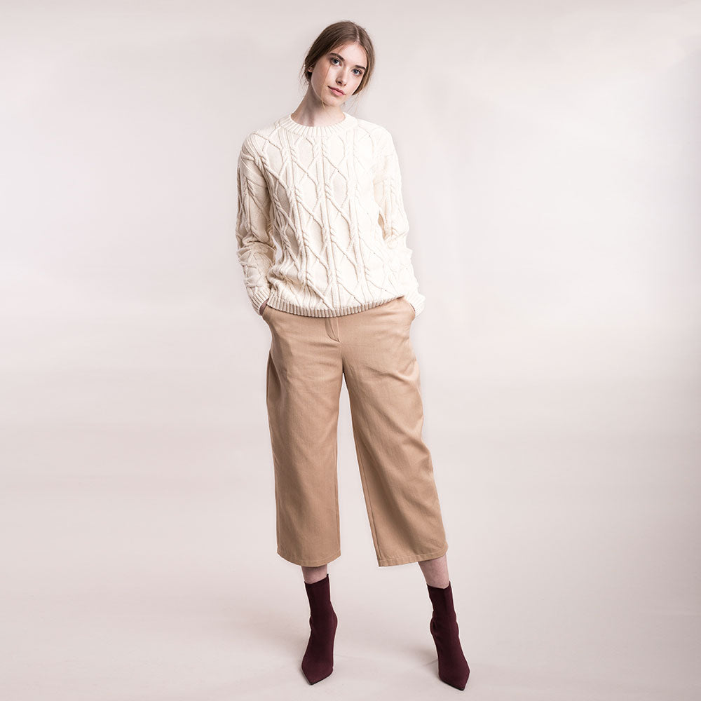 The model wears light brown, sustainable organic cotton, wide-leg trousers, front view.
