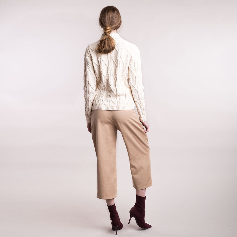 The model wears light brown, sustainable organic cotton, wide-leg trousers, back view.