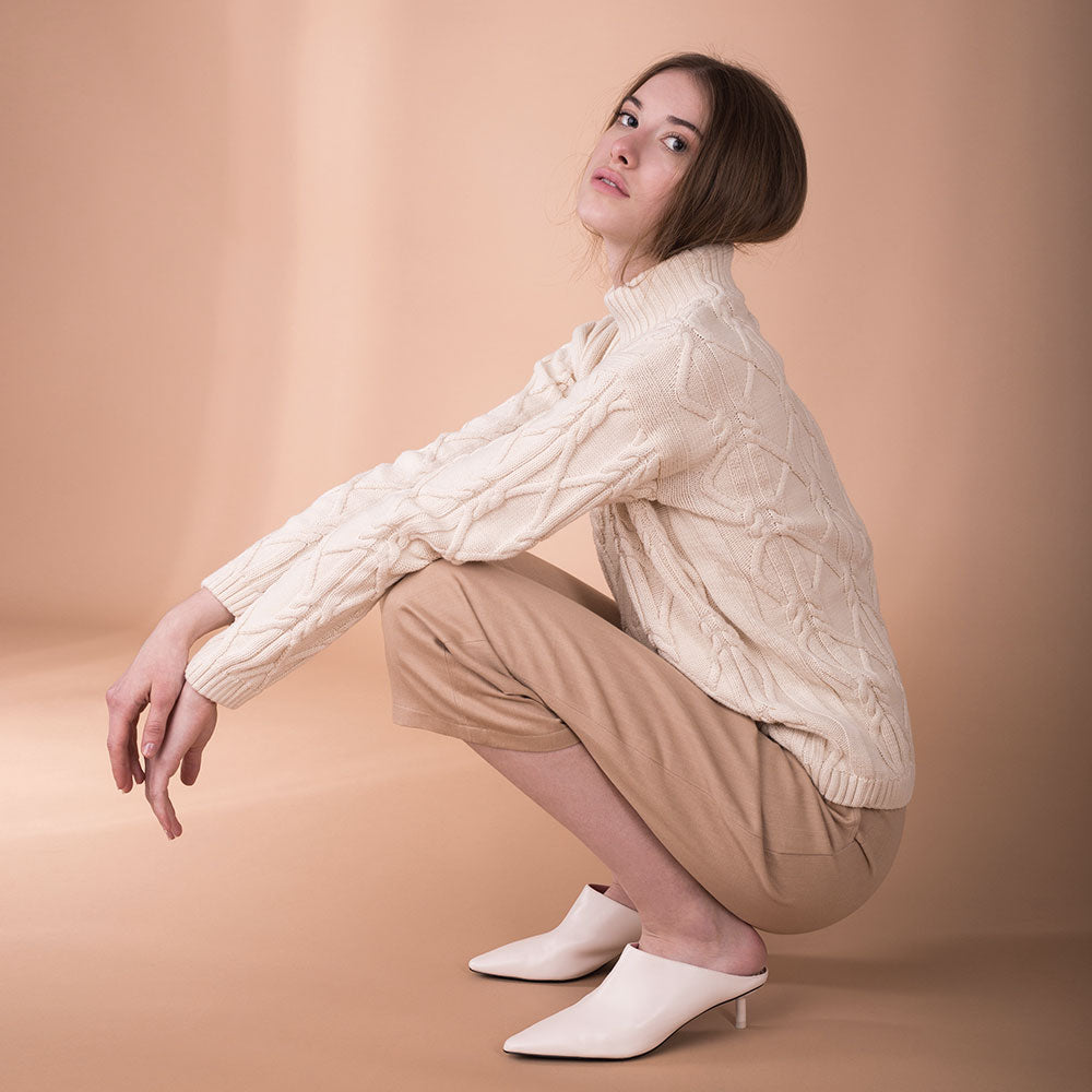The model wears light brown, sustainable organic cotton, wide-leg trousers, side view squat.
