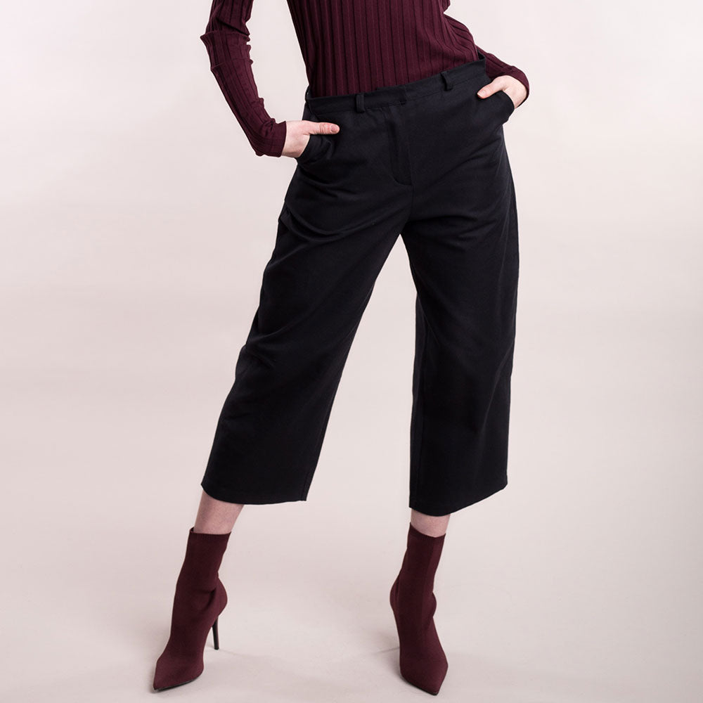 The model wears black, sustainable organic cotton, wide-leg trousers, front view close up.