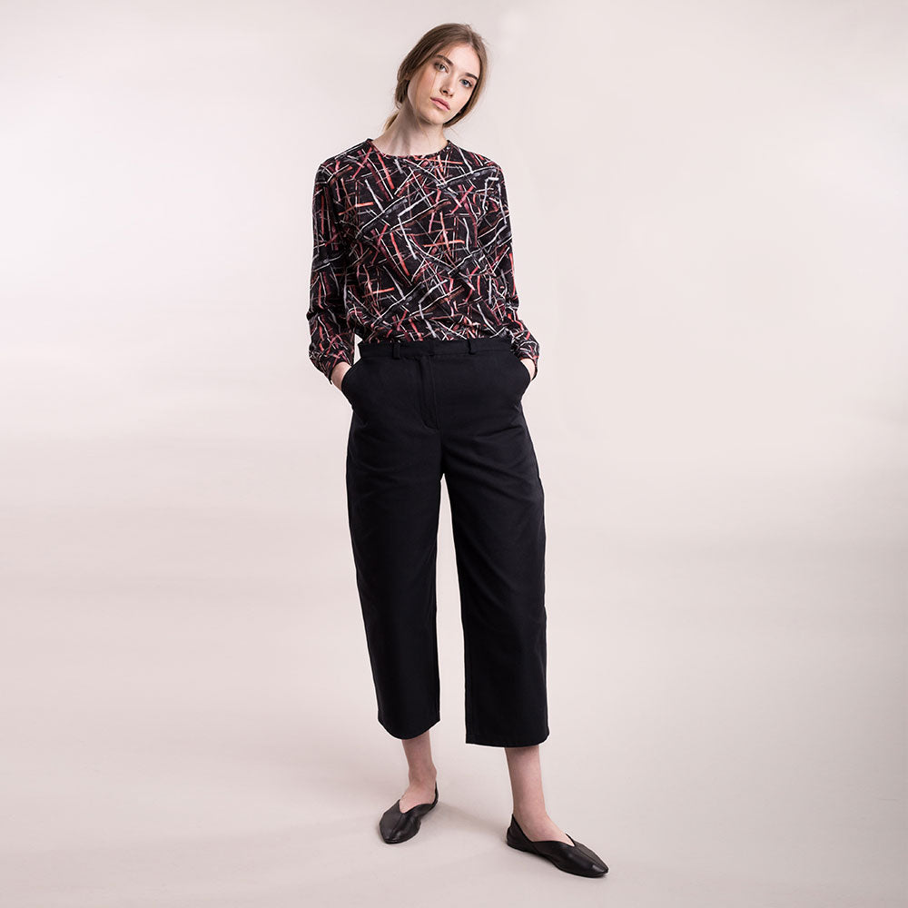 The model wears black, sustainable organic cotton, wide-leg trousers, front view.