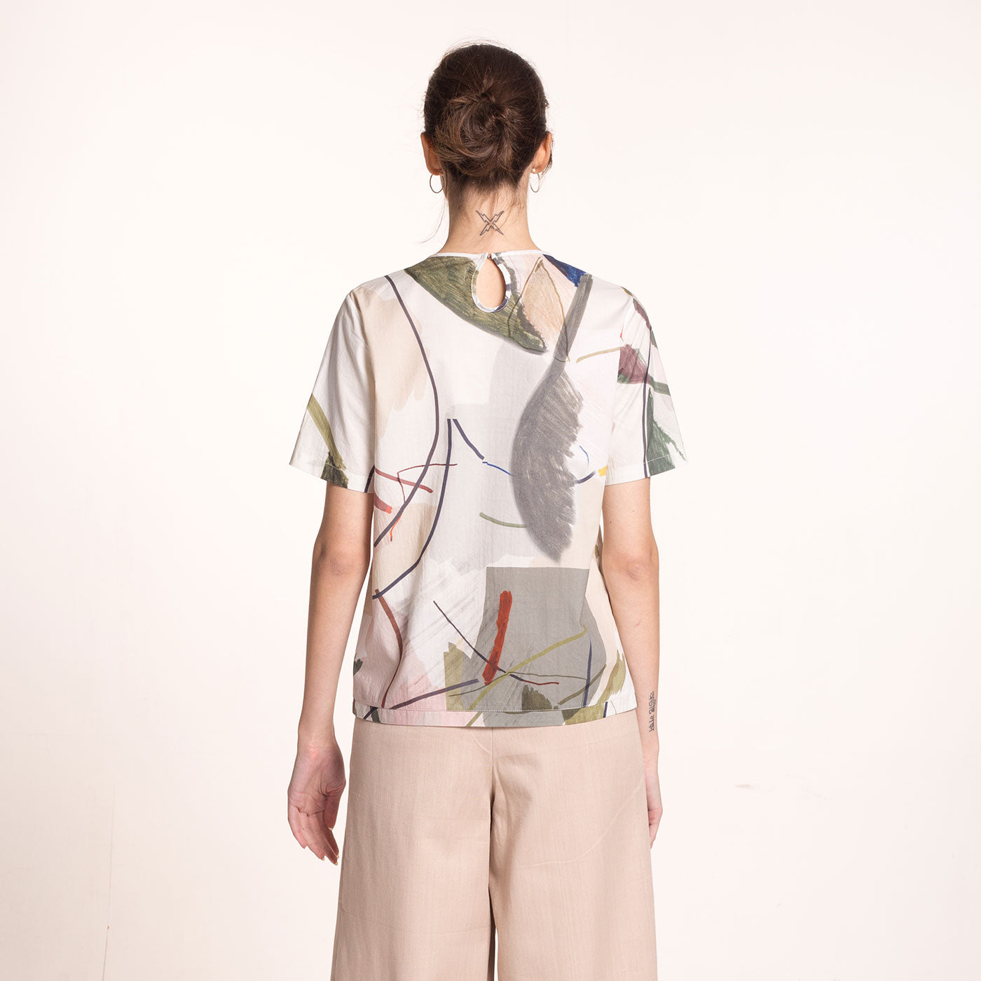 The model wears a sustainable, organic cotton, short sleeved blouse with round neckline and printed beige fabric with coloful shapes, back view.