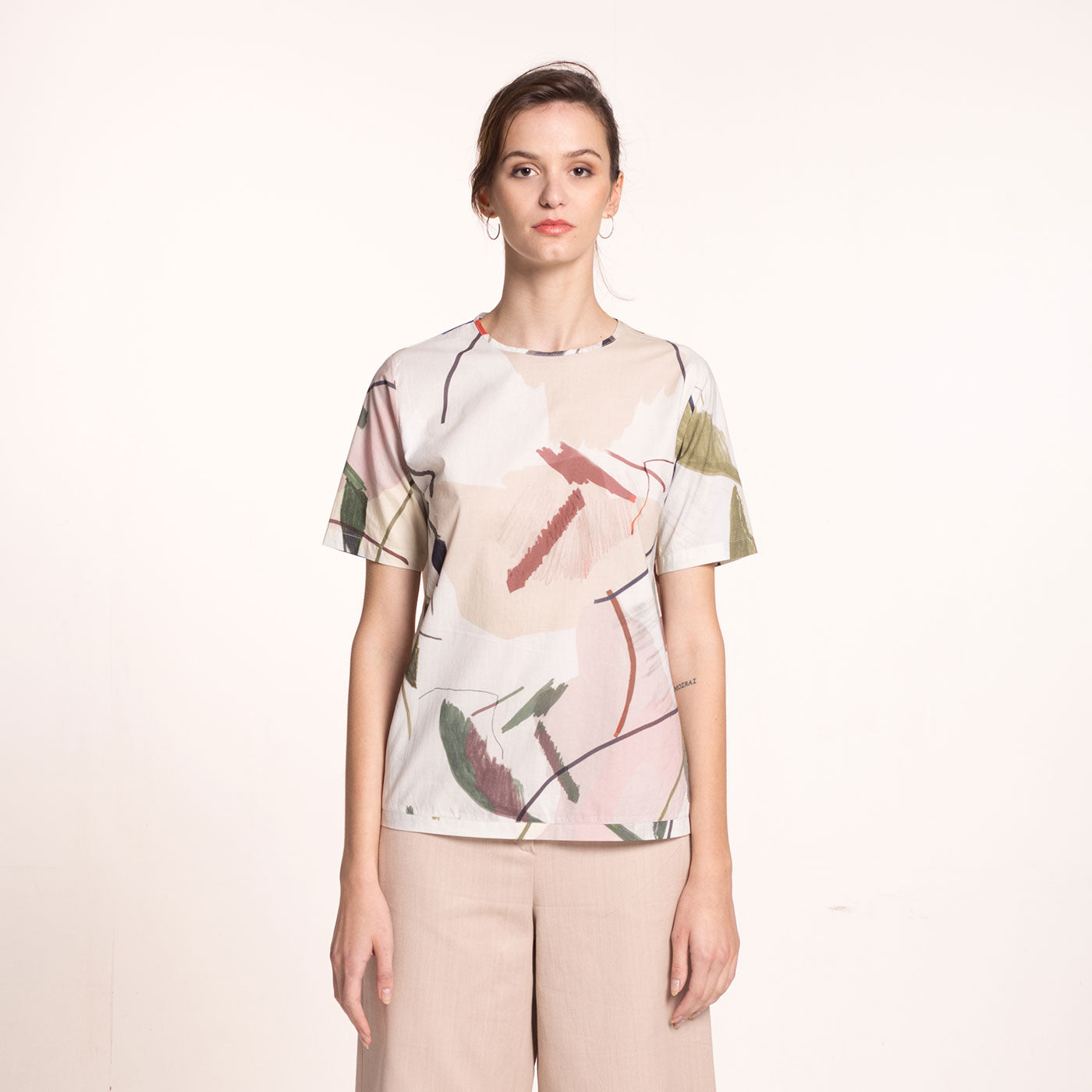 The model wears a sustainable, organic cotton, short sleeved blouse with round neckline and printed beige fabric with coloful shapes, front view.