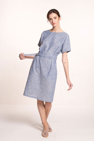 The model wears a light blue, sustainable, organic cotton and hemp dress, with short sleeves and round neckline and a fabric belt.