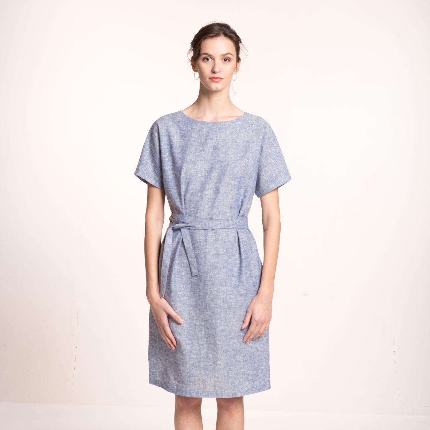 The model wears a light blue, sustainable, organic cotton and hemp dress, with short sleeves and round neckline and a fabric belt, front view