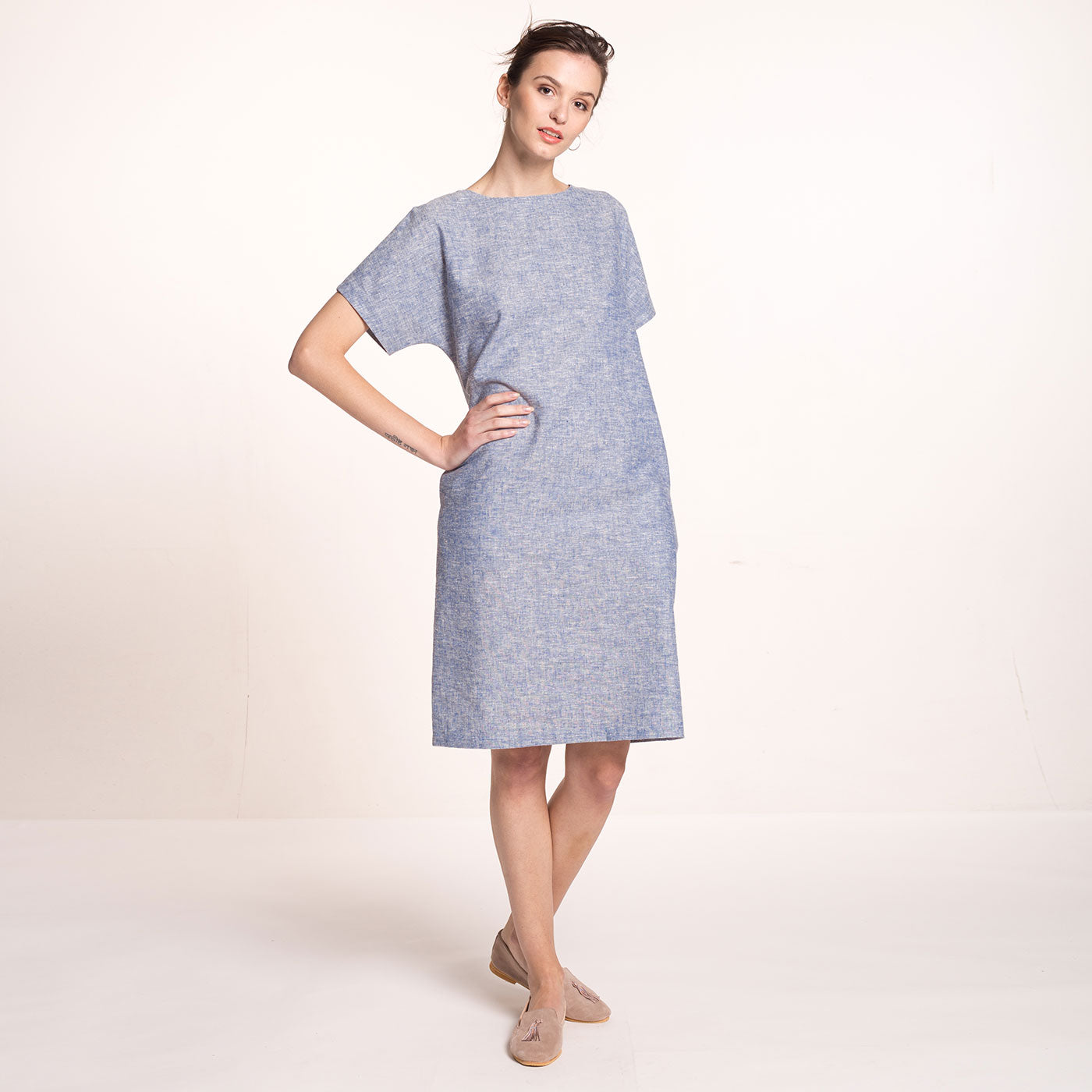 The model wears a light blue, sustainable, organic cotton and hemp dress, with short sleeves and round neckline at the front..