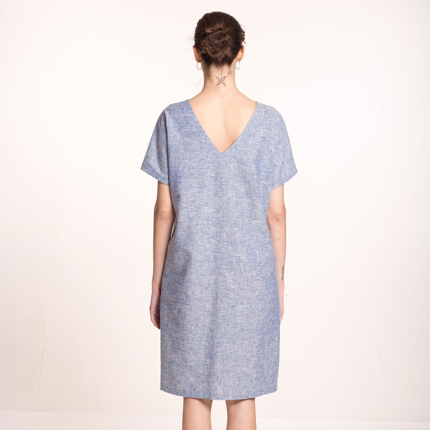 The model wears a light blue, sustainable, organic cotton and hemp dress, with short sleeves and V-neck at the back.