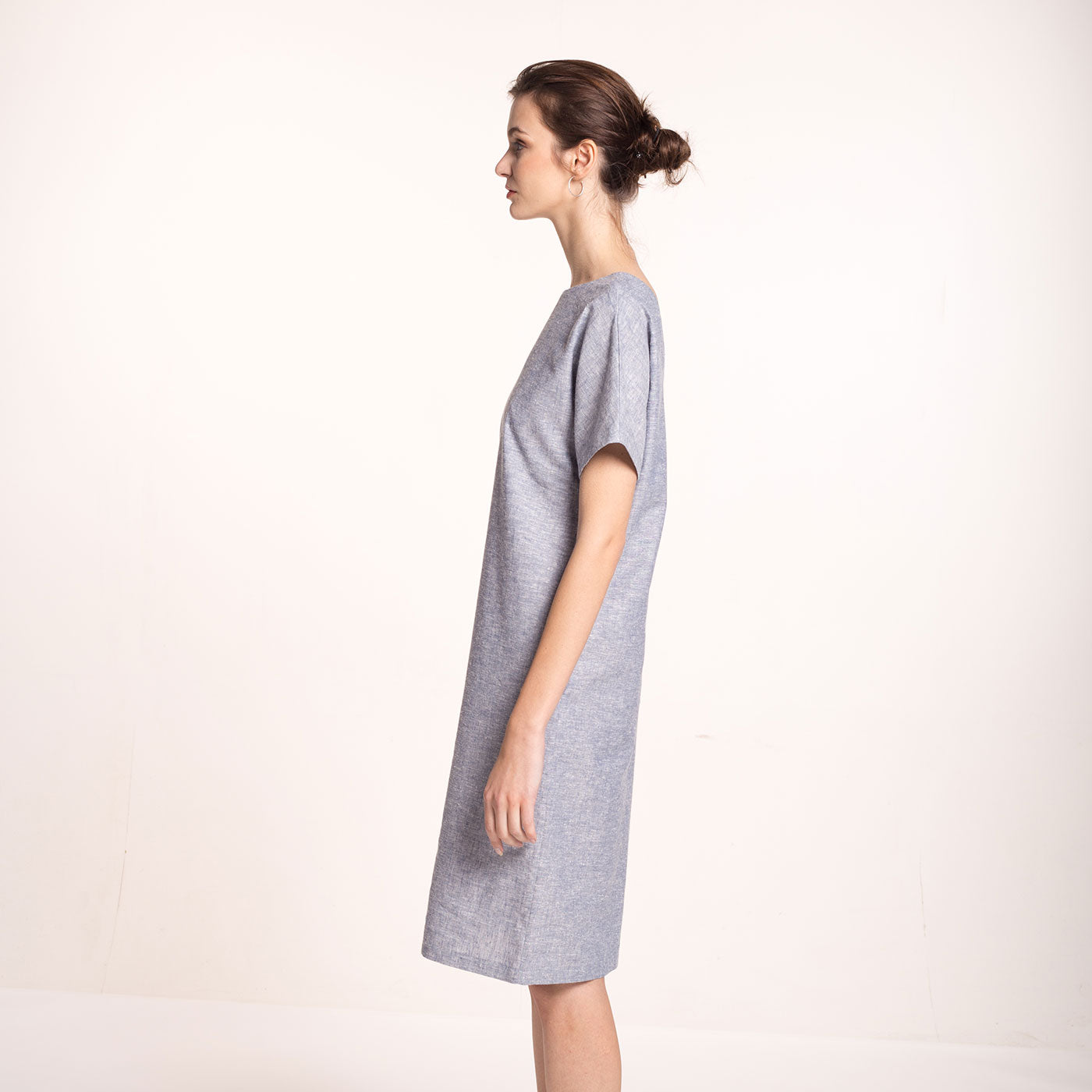 The model wears a light blue, sustainable, organic cotton and hemp dress, with short sleeves and round neckline, side view.