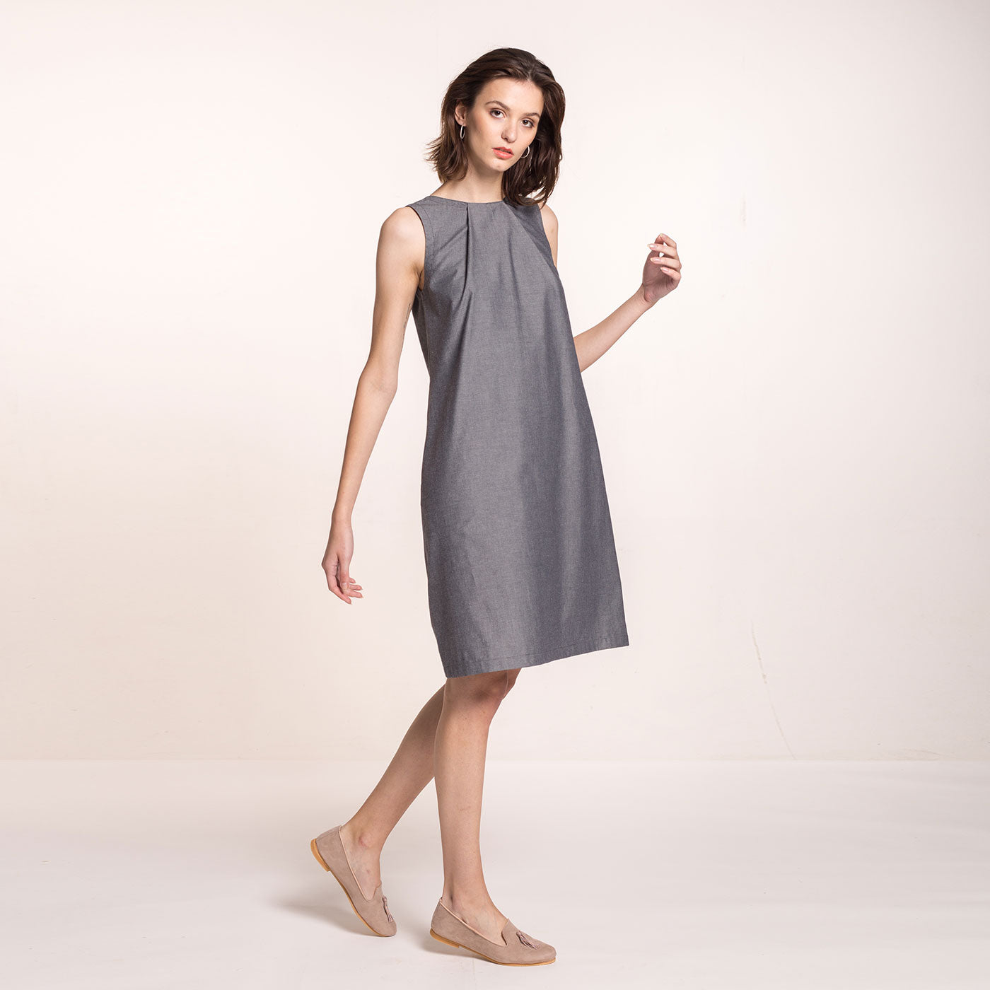The model wears a grey, sustainable,  organic cotton, A-line shape dress, with pleats on the round neckline and pockets, frontal view.