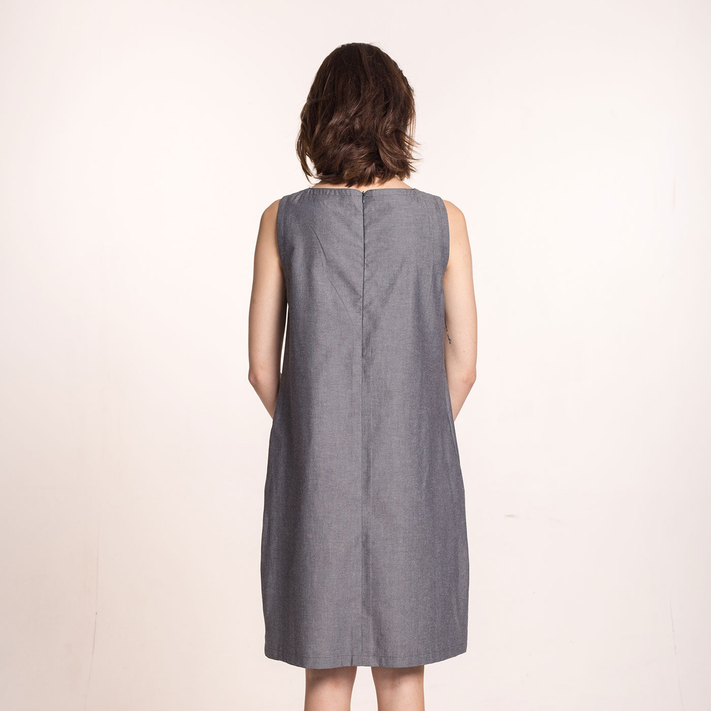 The model wears a grey, sustainable,  organic cotton, A-line shape dress, with pleats on the round neckline and pockets, back view.