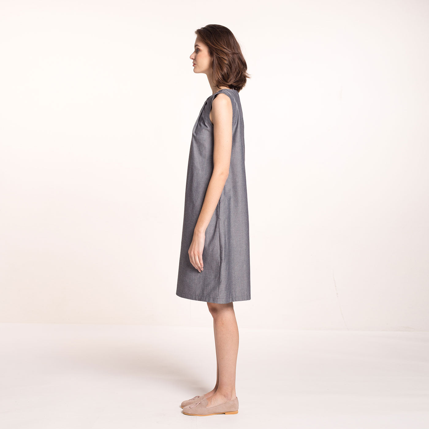 The model wears a grey, sustainable,  organic cotton, A-line shape dress, with pleats on the round neckline and pockets, side view.