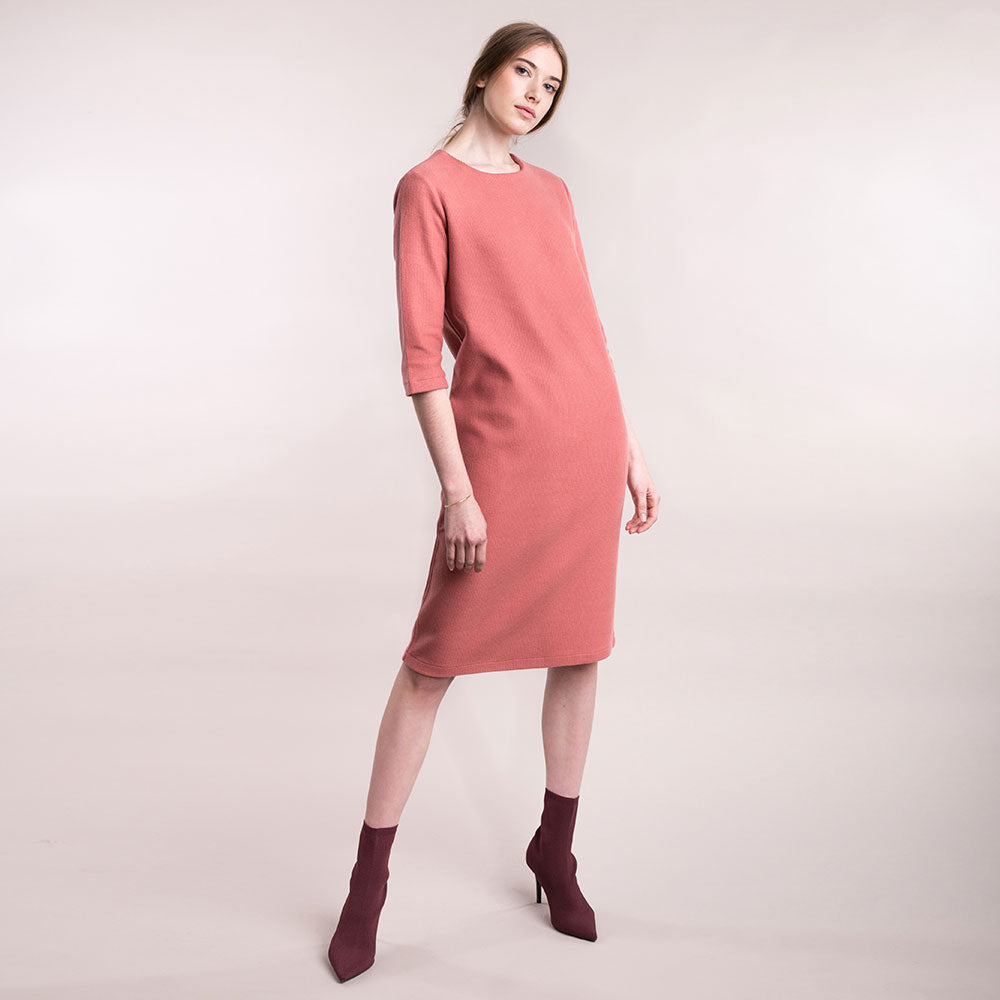 The model wears a peach, sustainable organic cotton, soft corduroy cocktail dress.