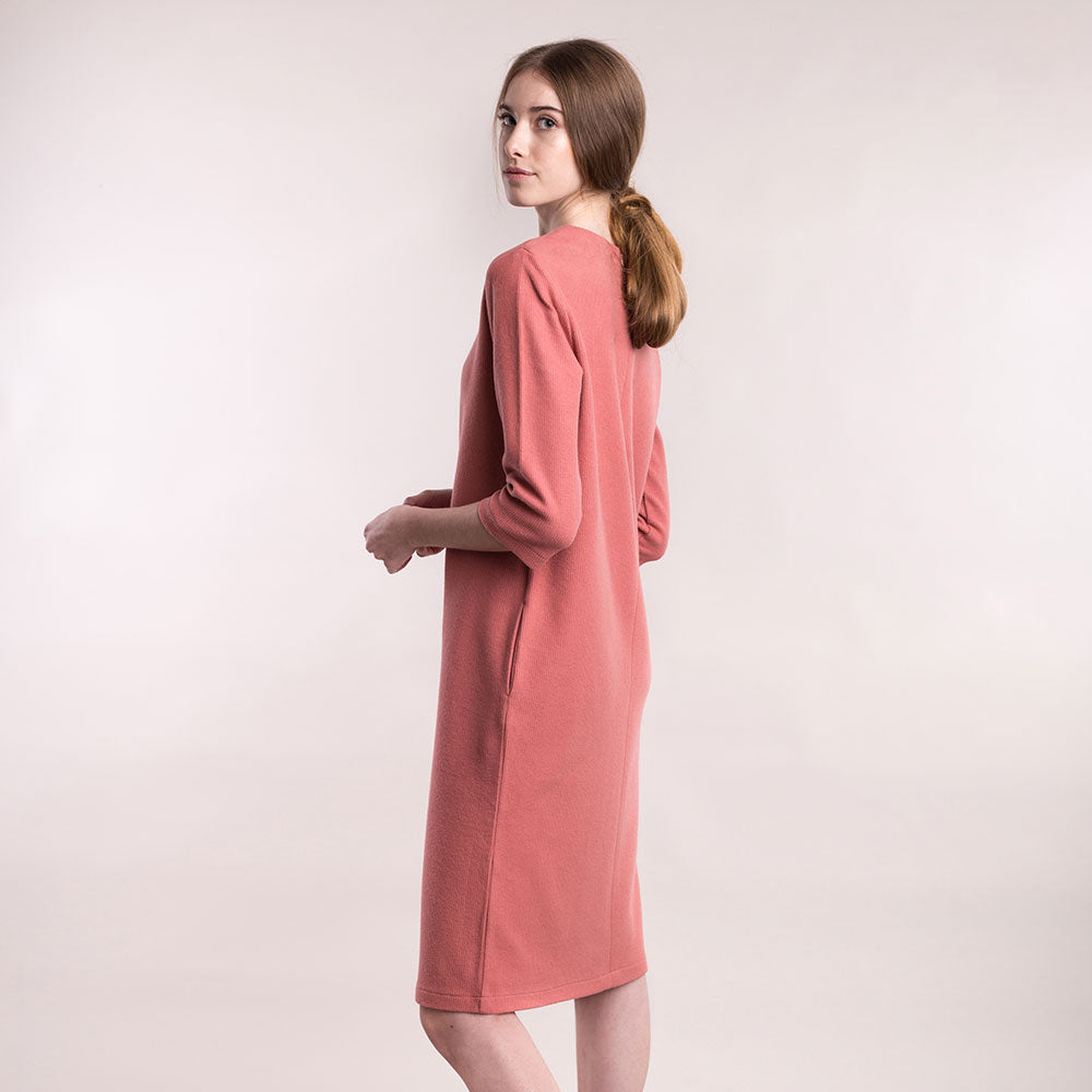 The model wears a peach, sustainable organic cotton, soft corduroy cocktail dress, back view close up.