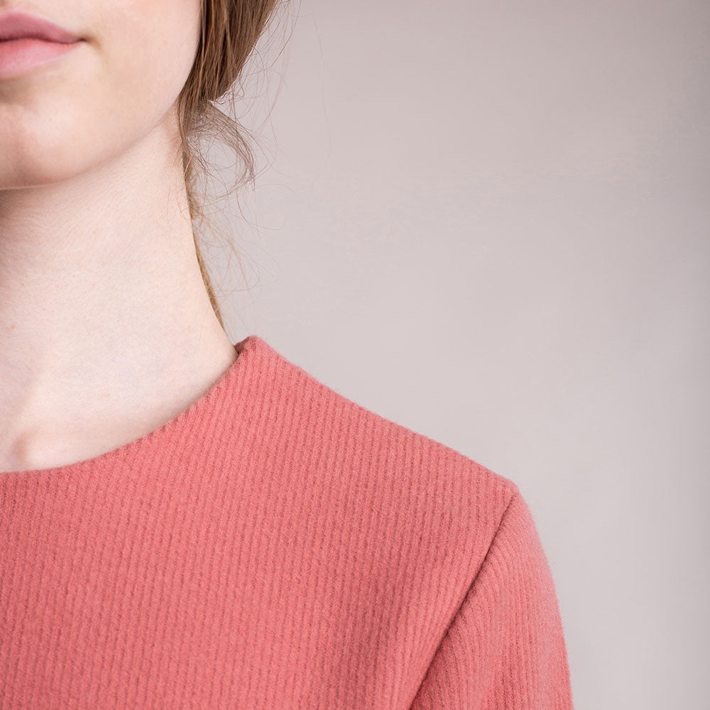 The model wears a peach, sustainable organic cotton, soft corduroy cocktail dress, detail round neckline.