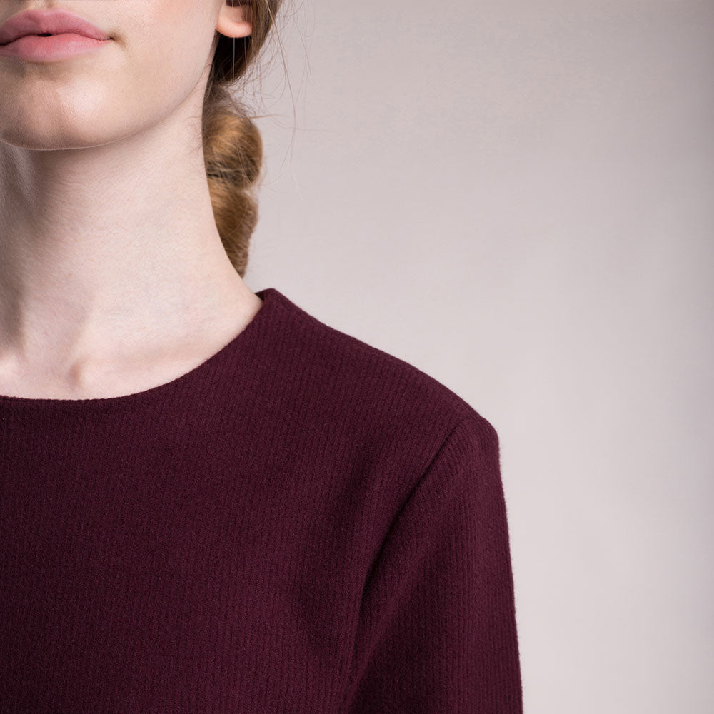 The model wears a burgundy, sustainable organic cotton, soft corduroy cocktail dress, detail round neckline.