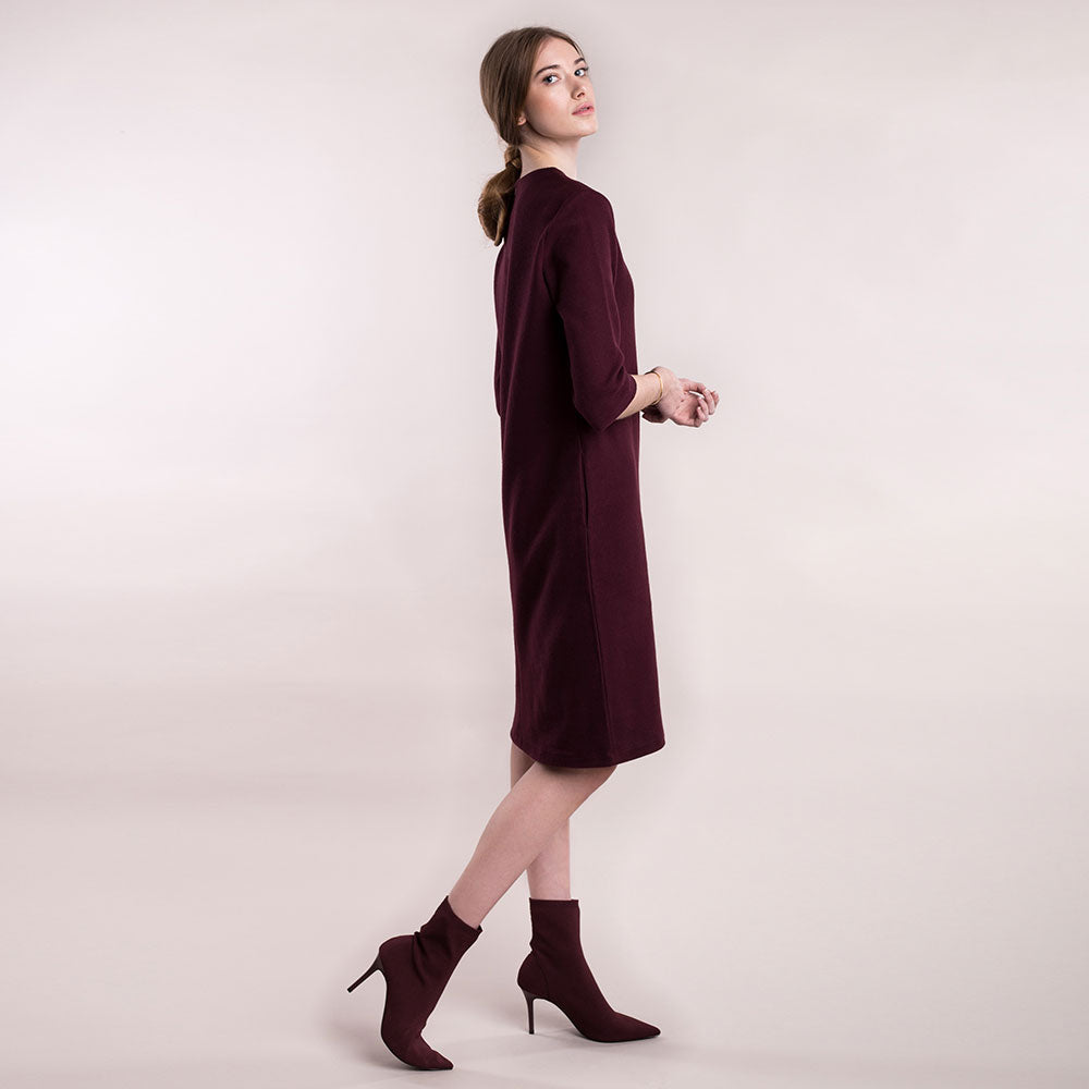 The model wears a burgundy, sustainable organic cotton, soft corduroy cocktail dress, back view.