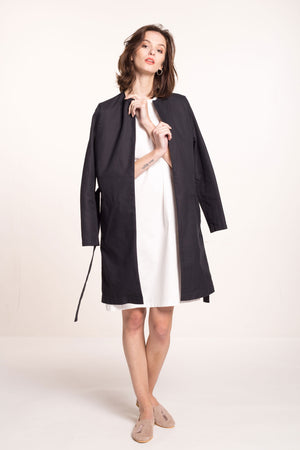 The model wears a black, sustainable cotton coat over a white dress.