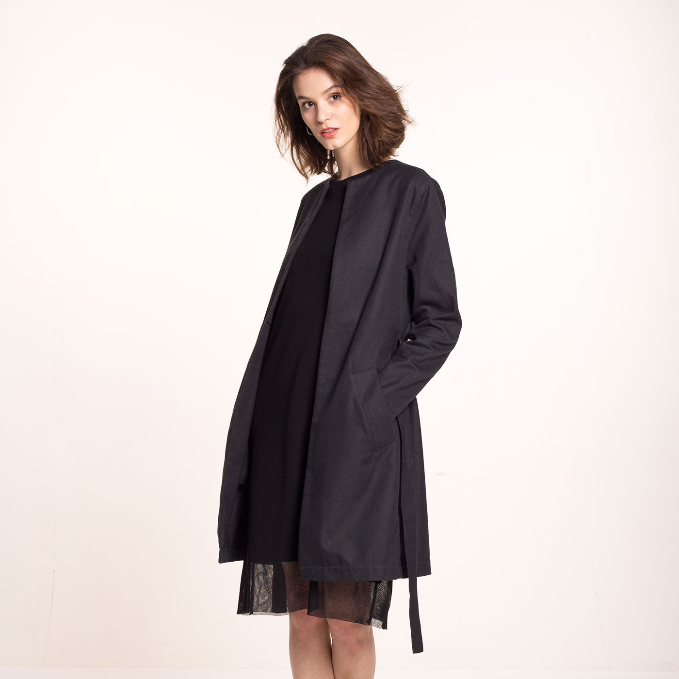 The model wears a black, sustainable cotton coat, with round neckline, straight fit and a belt, over a black dress..