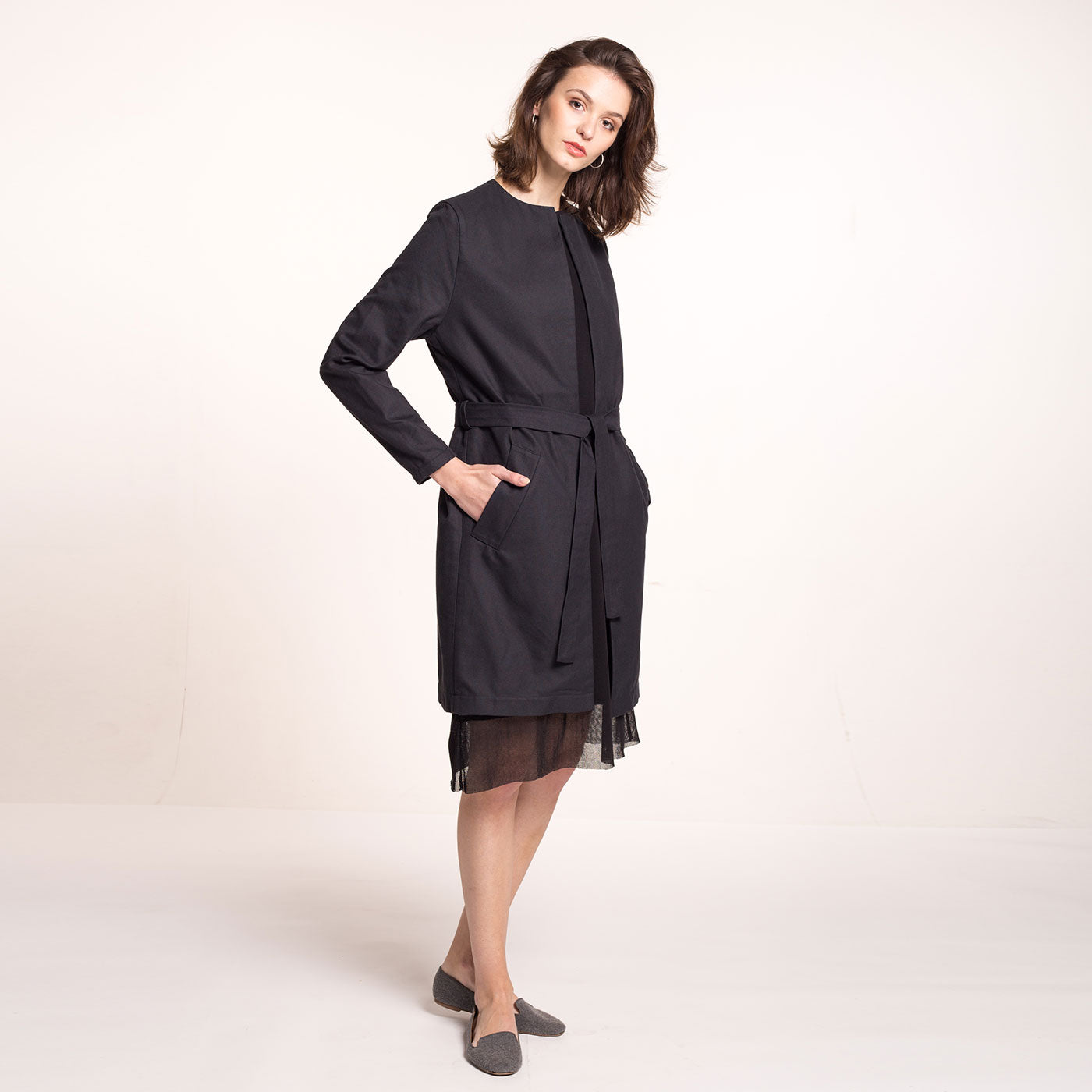 The model wears a black, sustainable cotton coat, with round neckline, straight fit and a belt, side view.