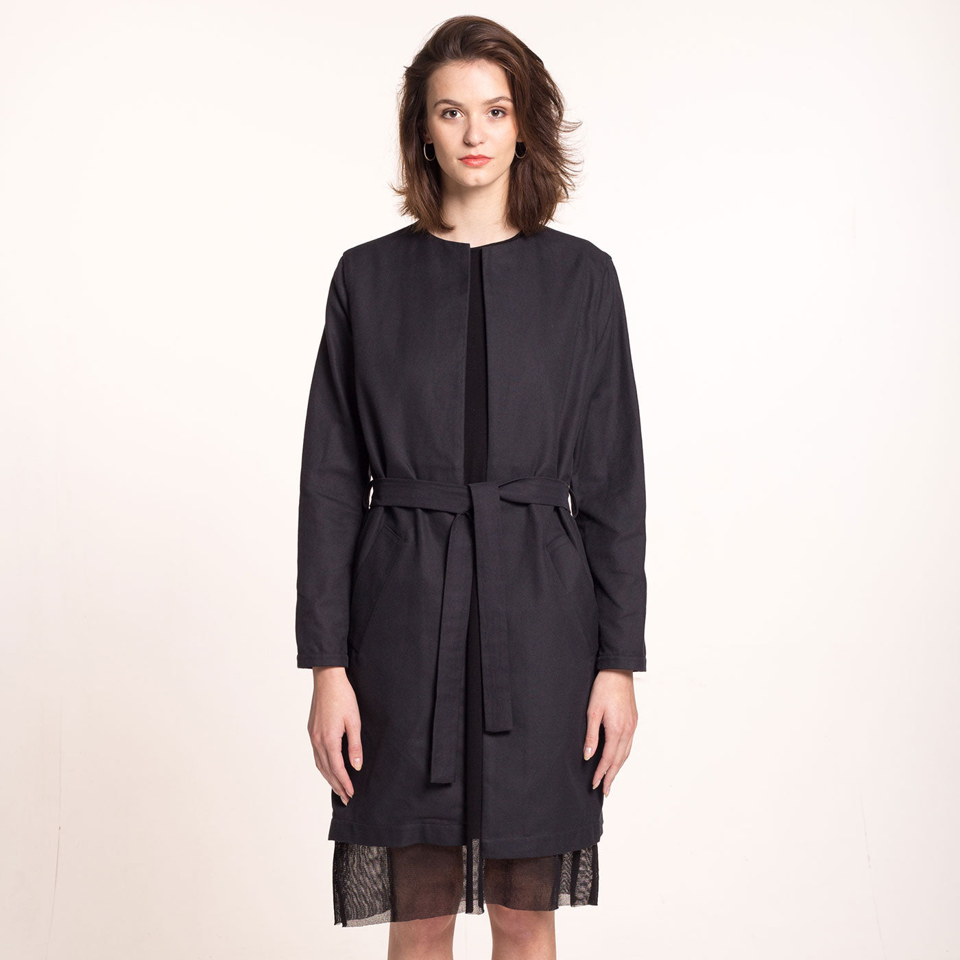 The model wears a black, sustainable cotton coat, with round neckline, straight fit and a belt, front view.