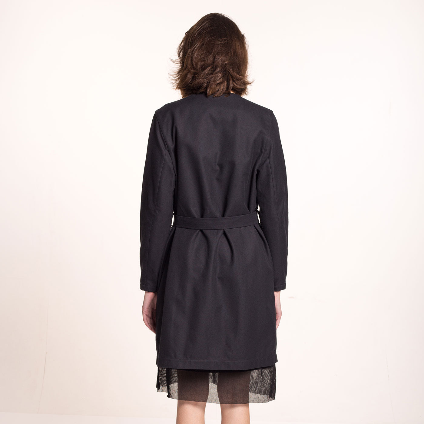 The model wears a black, sustainable cotton coat, with round neckline, straight fit and a belt, back view.