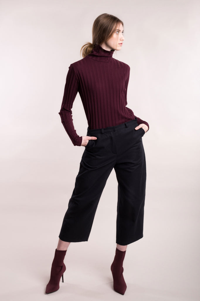 The model wears black, sustainable organic cotton, wide-leg trousers.